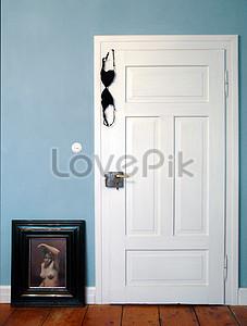 A Girls Black Bra Hanging To The Bedroom Door Image
