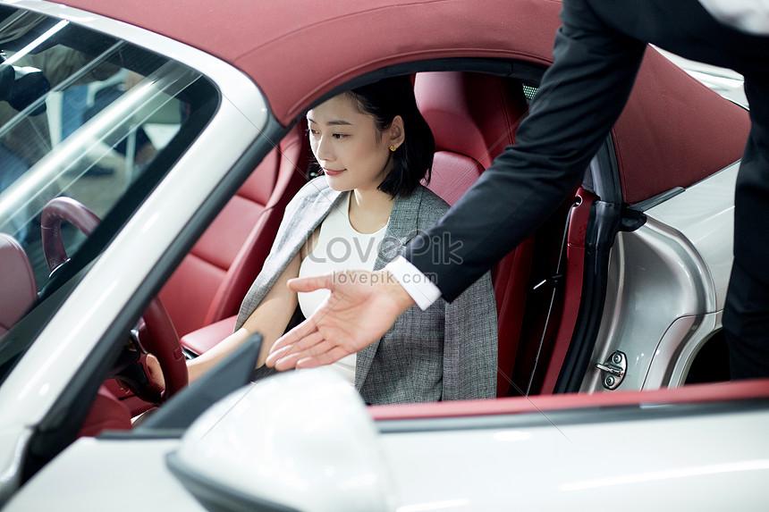 汽車銷售服務人員為客户介紹汽車