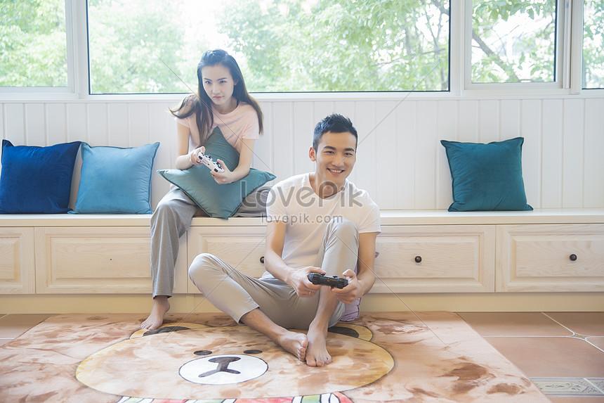 年輕情侶在客廳打遊戲