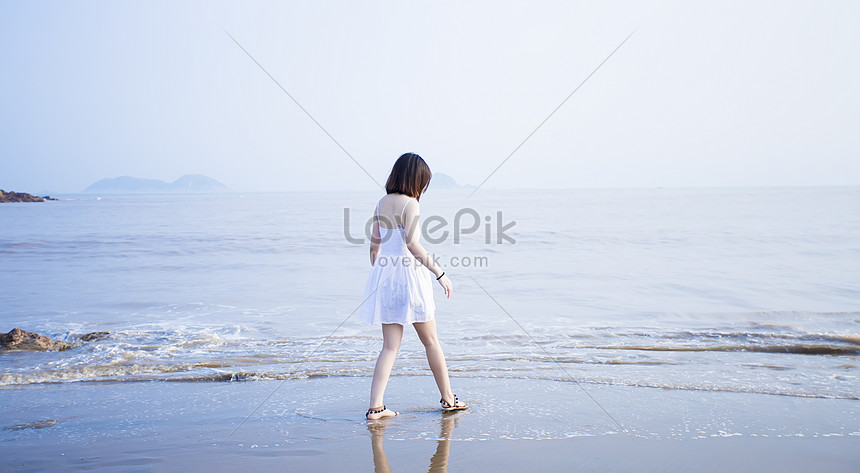 a girl walking by the sea