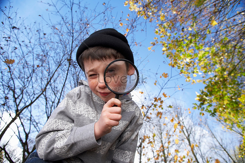batang lalaki na may magnifying glass
