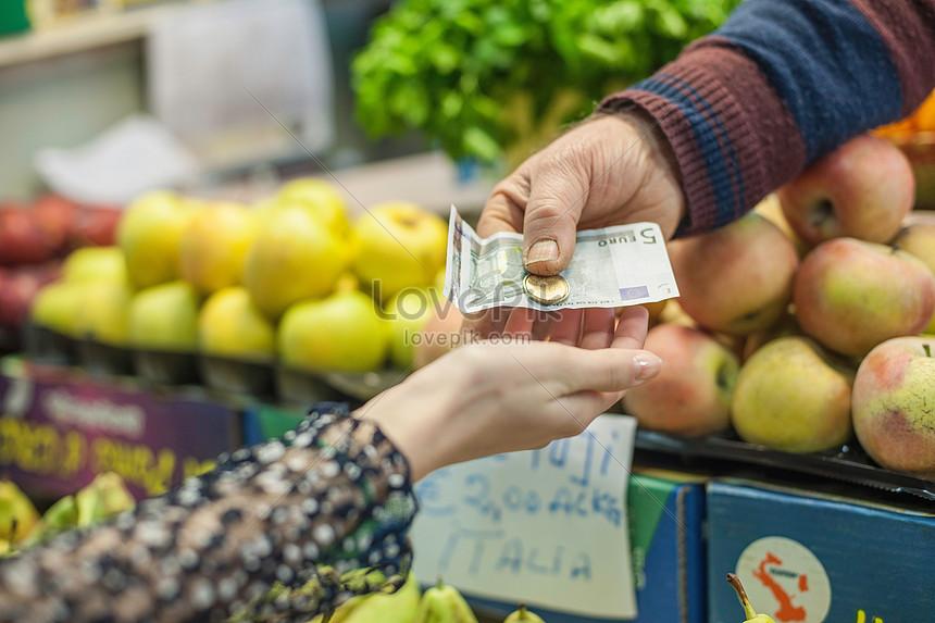 pemilik memberikan perubahan kepada pelanggan wanita di pasar