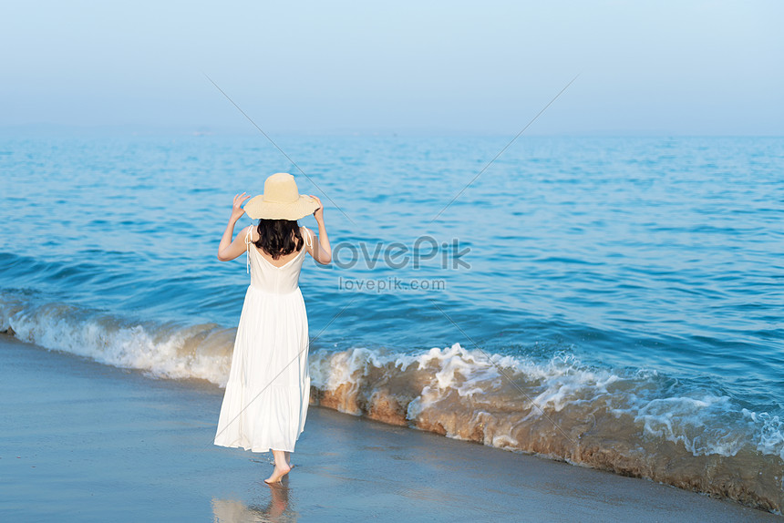 wanita cantik berjalan di pantai di tepi laut