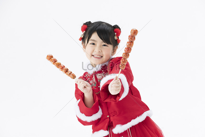 cute little girl holding candied haws in both hands