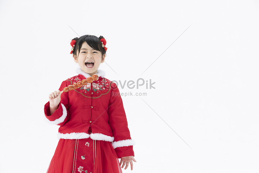 little girl with open mouth eating candied haws