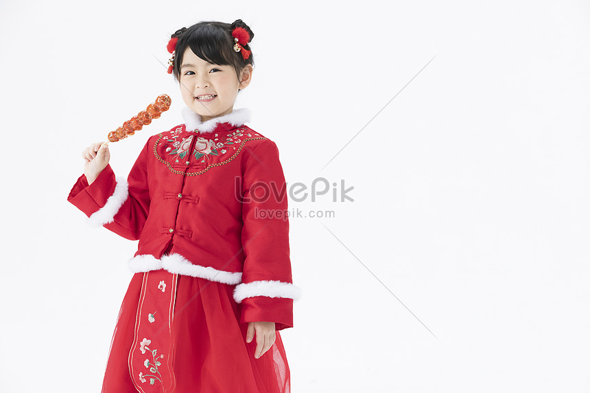 little girl holding candied haws in one hand smiling happily
