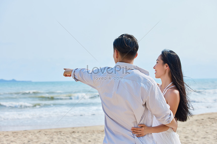 young couple walking on the sea walking back